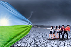 Business teamwork changing reality. Business team is pulling summer season background to change drought season Royalty Free Stock Image