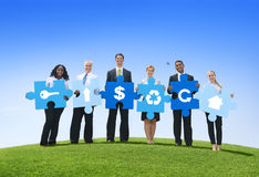 Business Teamwork With Jigsaw Puzzle. Group of Business People Holding Puzzle Pieces with Icons in an Open Field Royalty Free Stock Image