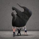Business teamwork lifting elephant on grey. Business people lifting an elephant together on grey background Royalty Free Stock Photography