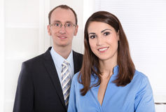 Business teamwork - man and woman on white with blue. Portrait of a successful business team - he in suit and tie and she smiling in a blue blouse - teamwork Royalty Free Stock Images