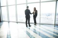 Business, teamwork, partnership, cooperation and people concept - business people shaking hands over panoramic office Stock Images
