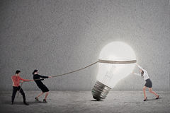 Business teamwork pull light bulb. Business teamwork is pulling a bright light bulb on grey background Stock Images