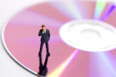 Business technology. Business figurine standing on a compact disk stock photos
