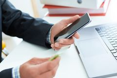 Male hands holding smart phone and credit card at office. Business, technology, cash free and internet people concept - Royalty Free Stock Image