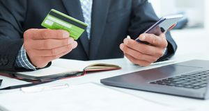 Male hands holding smart phone and credit card at office. Business, technology, cash free and internet people concept - Royalty Free Stock Images