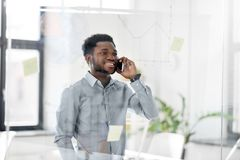 Businessman calling on smartphone at office. Business, technology, communication and people concept - african american businessman calling on smartphone and Royalty Free Stock Photos