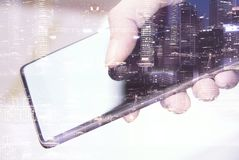 Hand using smartphone with cityscape background Royalty Free Stock Images