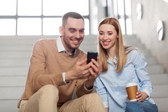 Man and woman with smartphone at office stairs Stock Photos