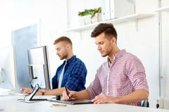 Designer with computer and pen tablet at office. Business, technology, design and people concept - young creative men or designer with computer and pen tablet Stock Photo