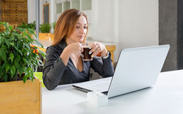Business, technology and green office concept - young successful businesswoman with laptop computer at office. Woman using tablet Royalty Free Stock Photography