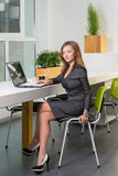 Business, technology and green office concept - young successful businesswoman with laptop computer at office. Woman using tablet. Computer or having a coffee Royalty Free Stock Photo