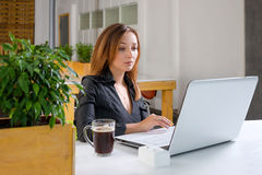 Business, technology and green office concept - young successful businesswoman with laptop computer at office. Woman using tablet. Computer or having a coffee Stock Photography
