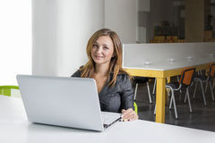 Business, technology and green office concept - young successful businesswoman with laptop computer at office. Woman using tablet Stock Images