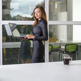Business, technology and green office concept - young successful businesswoman with laptop computer at office. Woman using tablet Royalty Free Stock Photos