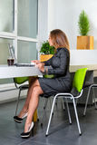 Business, technology and green office concept - young successful businesswoman with laptop computer at office. Woman using tablet Stock Photo