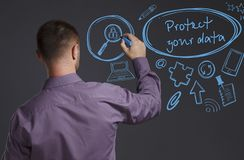Free Business, Technology, Internet And Network Concept. A Young Businessman Writes On The Blackboard The Word: Protect Your Data Stock Photography - 139392462