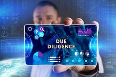 Business, Technology, Internet and network concept. Young businessman showing a word in a virtual tablet of the future: Due. Diligence stock photos
