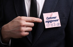 Business, Technology, Internet and network concept. Young businessman shows the word: Customer engagement stock photo