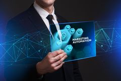 Business, Technology, Internet and network concept. Young busine. Ssman working on a virtual screen of the future and sees the inscription: Marketing automation Stock Photo