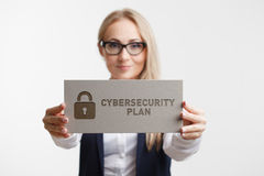 Business, Technology, Internet and network concept. Young girl holding a sign with an inscription CYBERSECURITY PLAN Royalty Free Stock Photo
