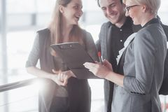 Business, technology and office concept - smiling female boss talking to business team stock photo