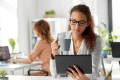 Businesswoman with tablet pc and coffee at office. Business, technology and people concept - african american businesswoman with tablet pc computer drinking Stock Photos