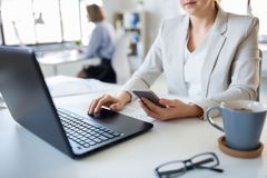 Businesswoman with smartphone and laptop at office royalty free stock photo