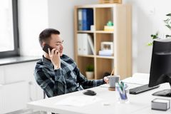 Creative male calling on smarphone at office Stock Image
