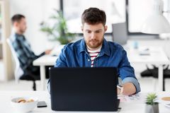 Creative man with laptop working at office Stock Photography