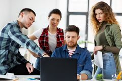 Creative team with laptop working at office Stock Photo