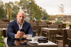 Business, technology and people concept - bald man with smartphone and coffee cup texting at city street cafe Stock Images