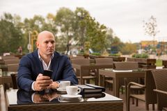 Business, technology and people concept - bald man with smartphone and coffee cup texting at city street cafe Stock Photography