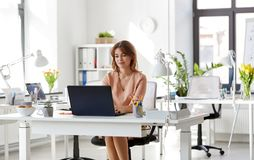 Happy businesswoman with laptop working at office. Business, technology and people concept - smiling businesswoman with laptop computer working at office Royalty Free Stock Photos
