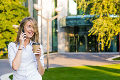 Business, technology and people concept - smiling businesswoman  with smartphone over office building Royalty Free Stock Photos