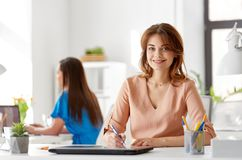 Smiling businesswoman working at office. Business, technology and people concept - smiling businesswoman working at office Royalty Free Stock Photos
