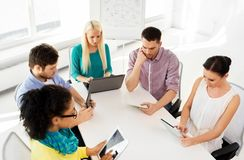 Creative team with table computers in office. Business, technology and startup concept - creative team with table pc computers in office royalty free stock images