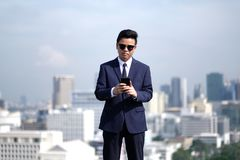 Business and technology. A young Asian businessman wearing a black suit and sunglasses use a smartphone to find information about his business people mobile royalty free stock image