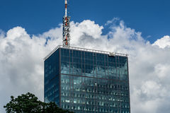 Business Telecomunication. Modern glass building, with huge radio antena in Belgrade. Dramatic skies contribute to more intense , business like feeling Stock Photography