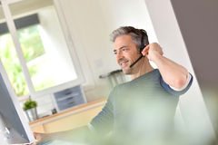 Business teleconference. Businessman in office using phone headset Royalty Free Stock Photo