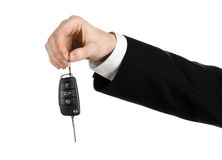 Business theme: car salesman in a black suit holding a car key isolated on white background Stock Image