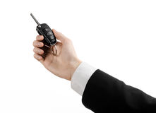 Business theme: car salesman in a black suit holding a car key isolated on white background Stock Photo