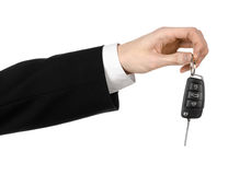 Business theme: car salesman in a black suit holding a car key isolated on white background Stock Photos
