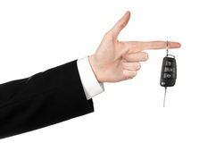 Business theme: car salesman in a black suit holding a car key isolated on white background Royalty Free Stock Photos