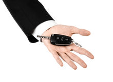 Business theme: car salesman in a black suit holding a car key isolated on white background Royalty Free Stock Images