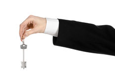 Business theme: real estate agent in the jacket in his hand the key to a new apartment on the white isolated background Royalty Free Stock Photos