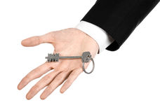 Business theme: real estate agent in the jacket in his hand the key to a new apartment on the white isolated background Royalty Free Stock Images