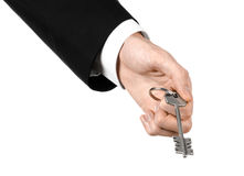 Business theme: real estate agent in the jacket in his hand the key to a new apartment on the white isolated background Stock Photos