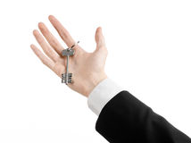 Business theme: real estate agent in the jacket in his hand the key to a new apartment on the white isolated background Royalty Free Stock Image