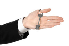 Business theme: real estate agent in the jacket in his hand the key to a new apartment on the white isolated background Royalty Free Stock Photo