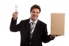 Business - Think outside the box. Think outside the box...  A business man balancing a box in one hand and holding an energy efficient ligh bulb in the other Royalty Free Stock Photo